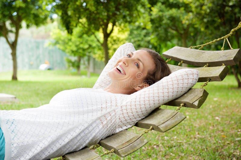 放松在吊床的微笑的老妇人户外 免版税库存照片