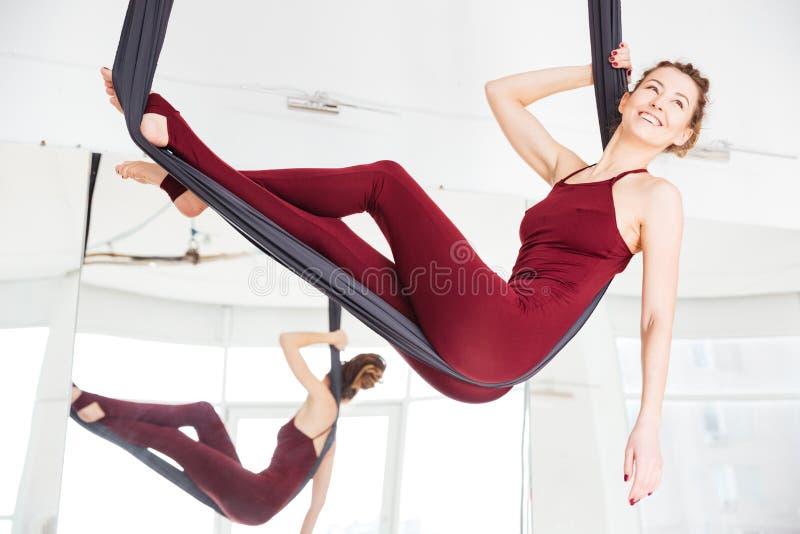 放松在吊床的愉快的妇女在反地心引力的瑜伽演播室 免版税图库摄影