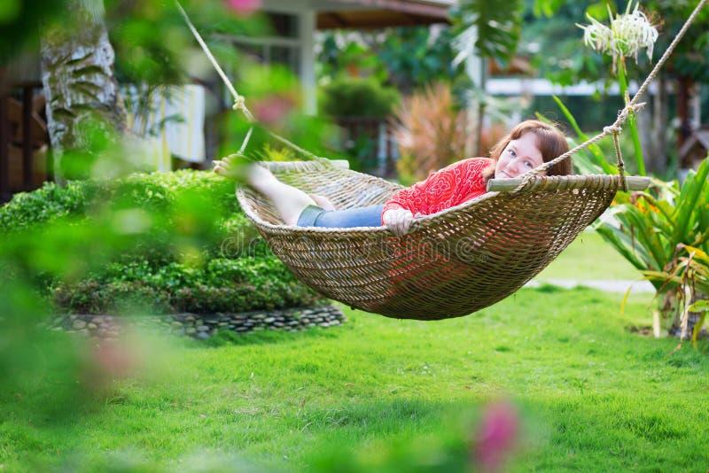 放松在吊床的愉快的美丽的妇女 免版税库存照片