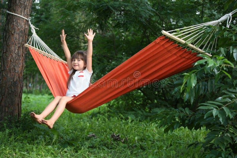 放松在吊床的逗人喜爱的女孩在夏日 免版税库存照片