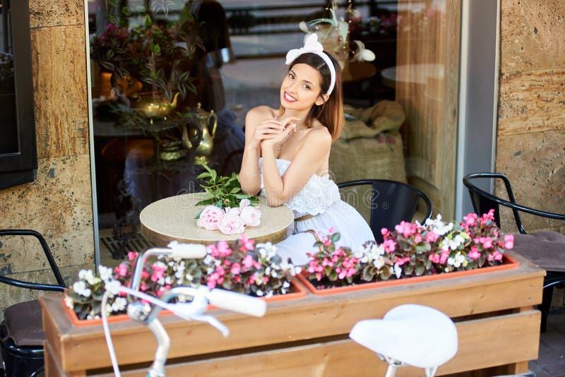 放松在咖啡馆的愉快的少妇户外 免版税库存照片