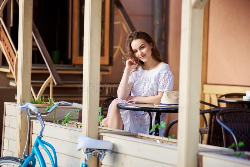放松在咖啡馆的愉快的少妇户外 库存图片