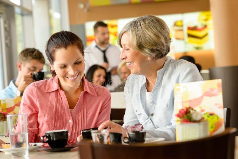 放松在咖啡馆的母亲和女儿 图库摄影