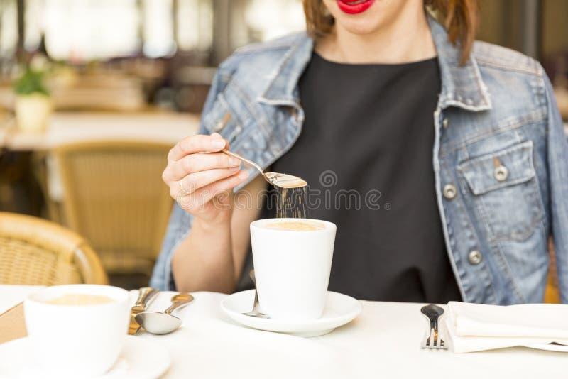 放松在咖啡馆的美丽的女孩,加糖入咖啡 免版税图库摄影