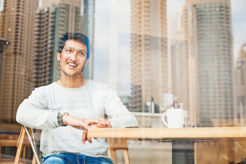 放松在咖啡馆的英俊的年轻印地安人 免版税库存照片