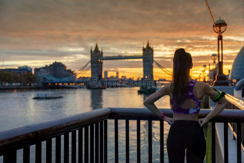 放松在城市赛跑和锻炼户外以后的健身妇女在伦敦,英国 免版税库存图片