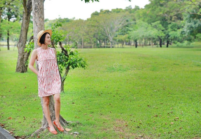 放松在夏天庭院里的愉快的年轻亚裔妇女 库存照片