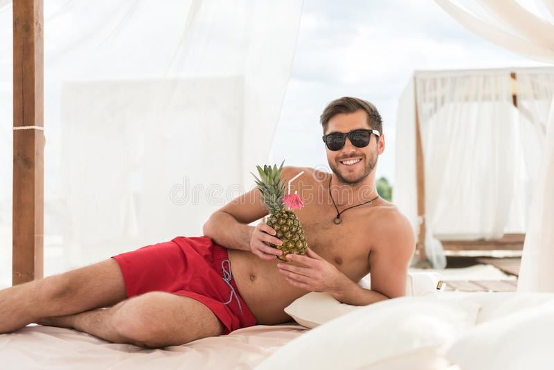 放松在夏天海滩的爽快年轻的有胡子的人 免版税库存照片