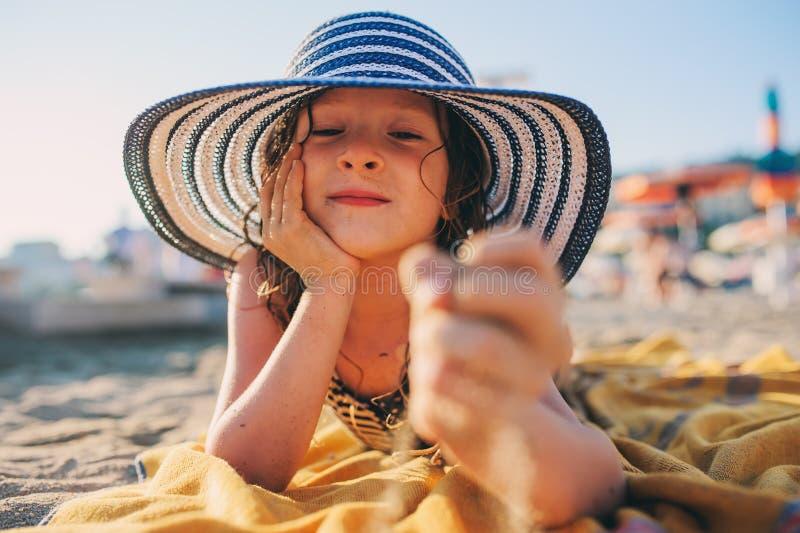 放松在夏天海滩,说谎在毛巾和使用与沙子的泳装的愉快的孩子 温暖的天气,舒适心情 旅行 图库摄影