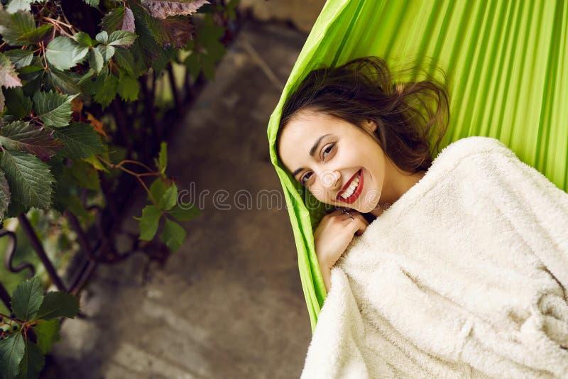 放松在大阳台房子的一个吊床的微笑的年轻女人画象 免版税库存照片
