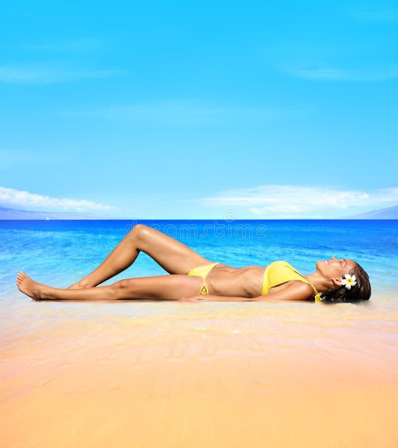 放松在太阳下的海滩旅行晒日光浴的妇女 免版税库存照片