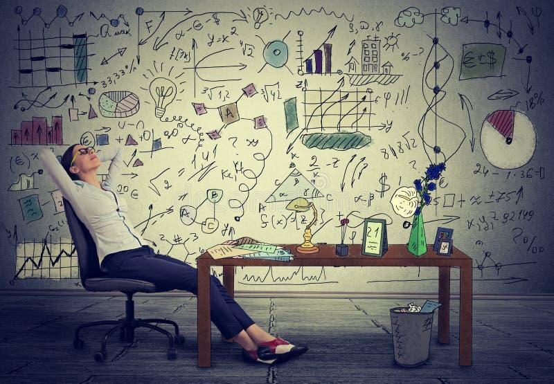 放松在她的书桌的女商人在她的办公室 免版税库存图片