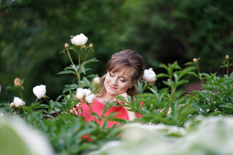 放松在她的有开花的花的庭院里的微笑的愉快的白种人妇女 库存照片
