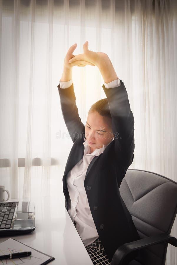 放松在她的椅子的成功的女实业家在办公室 库存图片