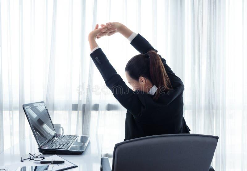 放松在她的椅子的成功的女实业家在办公室 库存照片