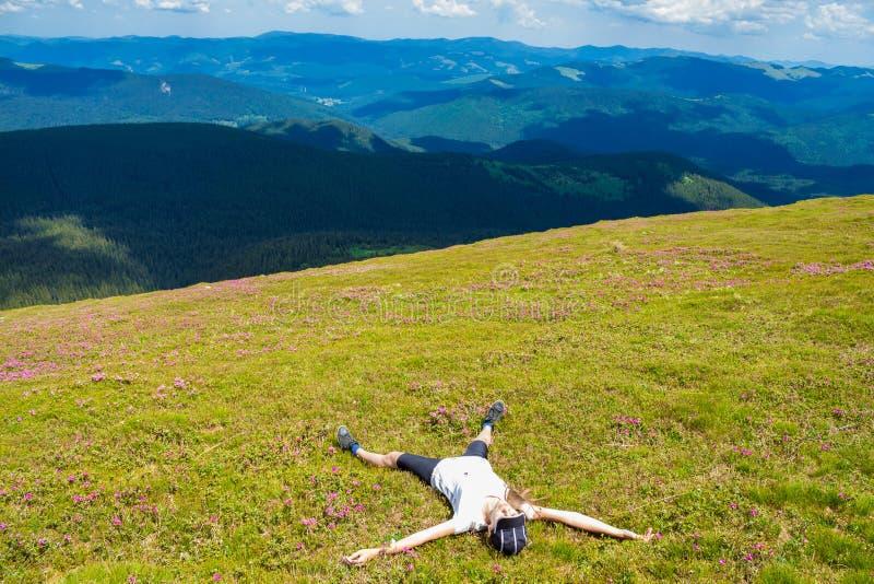 放松在小山和赞赏的美好的山谷视图上面的少妇远足者  免版税库存图片