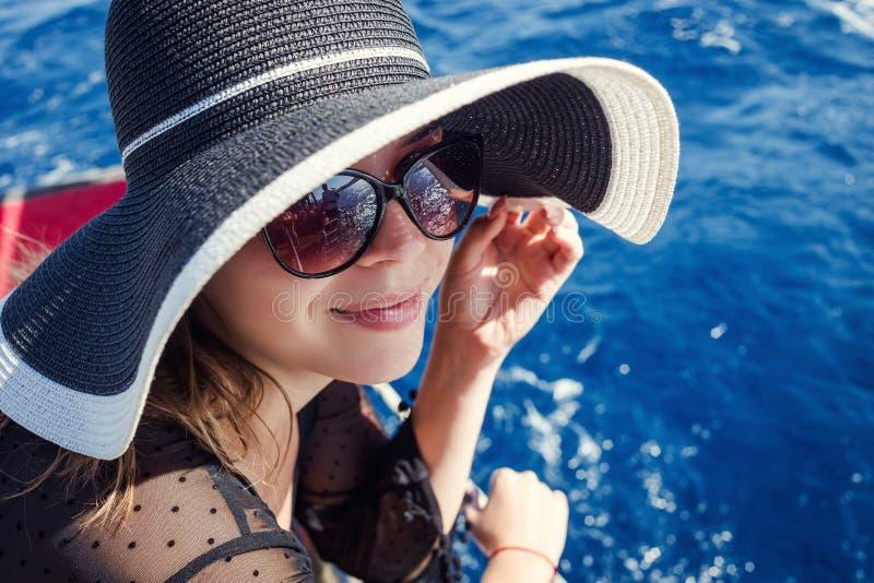 放松在小船和看的帽子的美丽的女孩是 库存图片