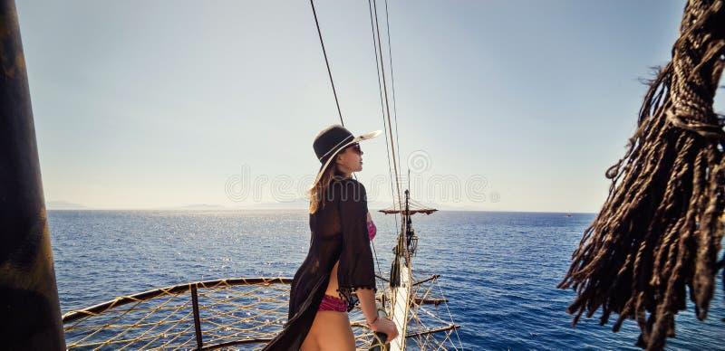 放松在小船和看的帽子的美丽的女孩是 免版税库存图片