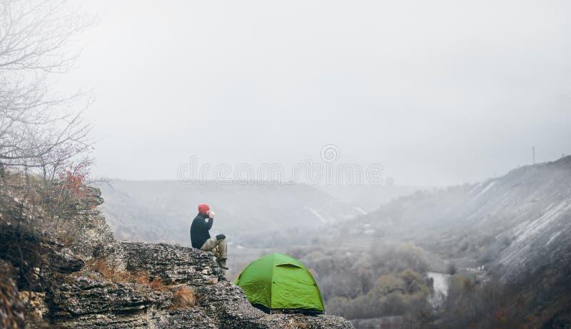 放松在山的风景观点的人旅客近室外帐篷的露营齿轮 男性放松在远足在以后 免版税库存图片