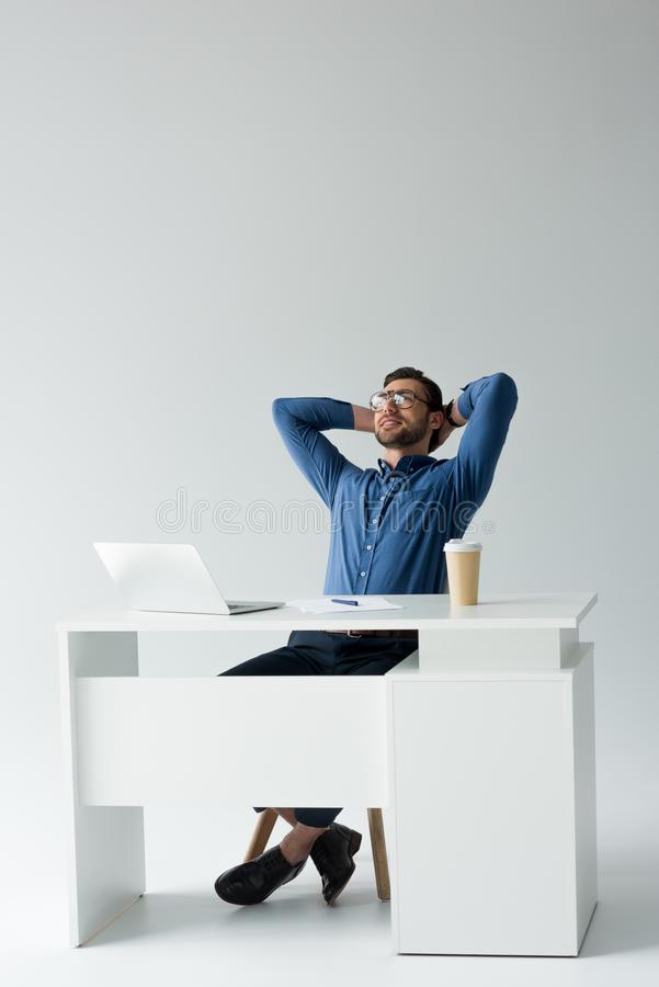 放松在工作场所的英俊的年轻商人 免版税库存图片