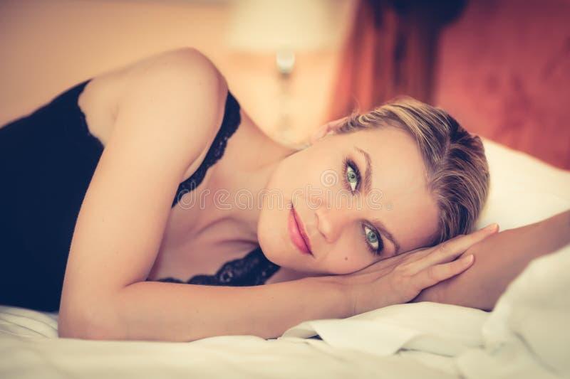 放松在床上的一个美丽的女孩的画象在旅馆客房 免版税库存照片