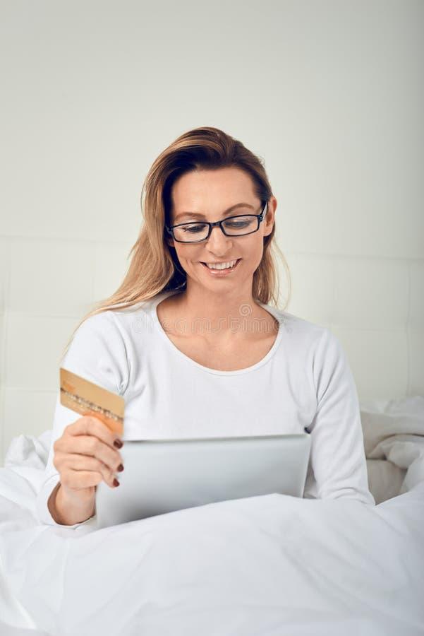 放松在床上的可爱的妇女做拿着她的信用卡的网上购物 免版税库存照片