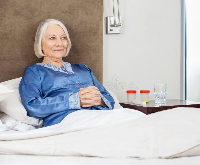 放松在床上的微笑的资深妇女在护理 免版税库存图片