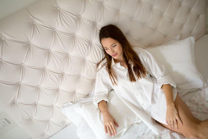 放松在床上的美丽的夫人 免版税库存照片