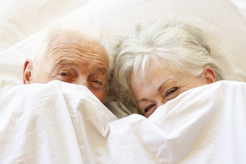 放松在床上的资深夫妇掩藏在板料下 免版税库存照片