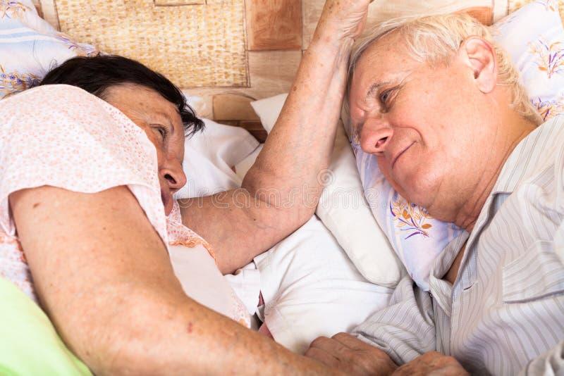 二个前辈在床上放松 库存照片