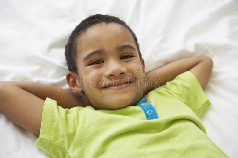 放松在床上的年轻男孩 免版税库存图片