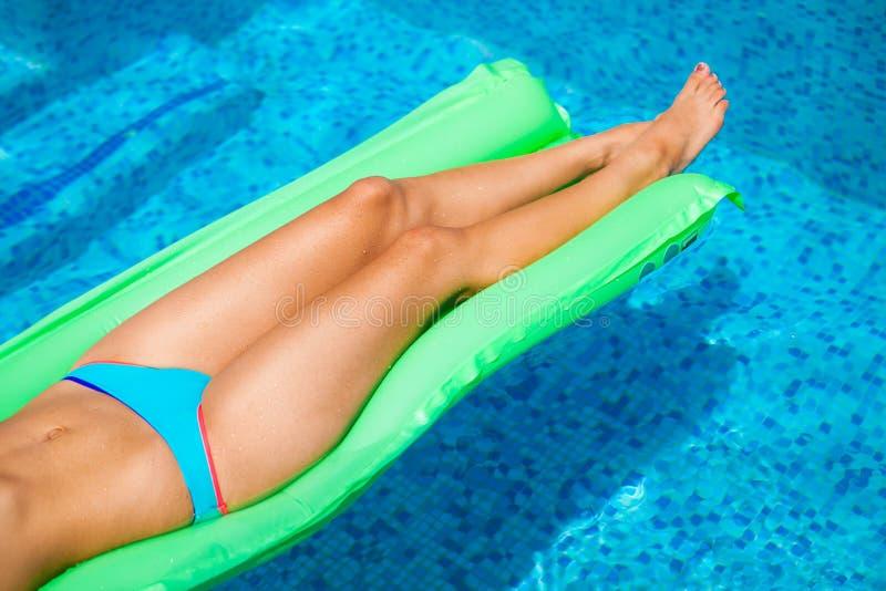 放松在床垫的妇女在水池水中在热的晴天 S 免版税库存照片