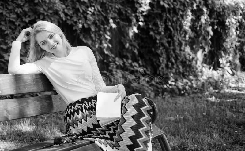 放松在庭院读书诗歌的妇女愉快的微笑的白肤金发的作为断裂 夫人在庭院里享受诗歌 享受押韵 ?? 库存照片