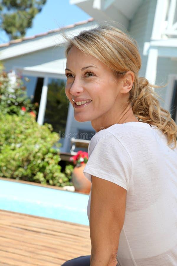 放松在庭院里的中年妇女由游泳池 免版税库存照片