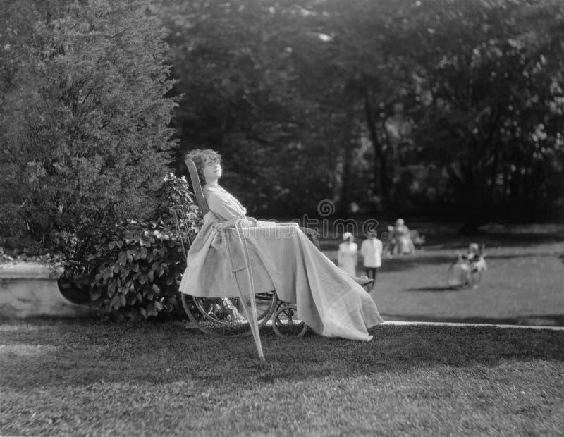 放松在庭院里的轮椅的女性患者(所有人被描述不更长生存,并且庄园不存在 供应商warran 免版税库存照片