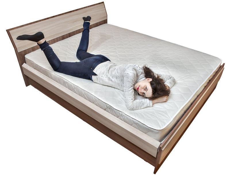 放松在弹簧床垫木床上的一名年轻白种人妇女 库存图片