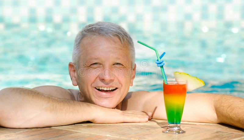 放松在手段游泳池的英俊的成熟人 免版税库存照片
