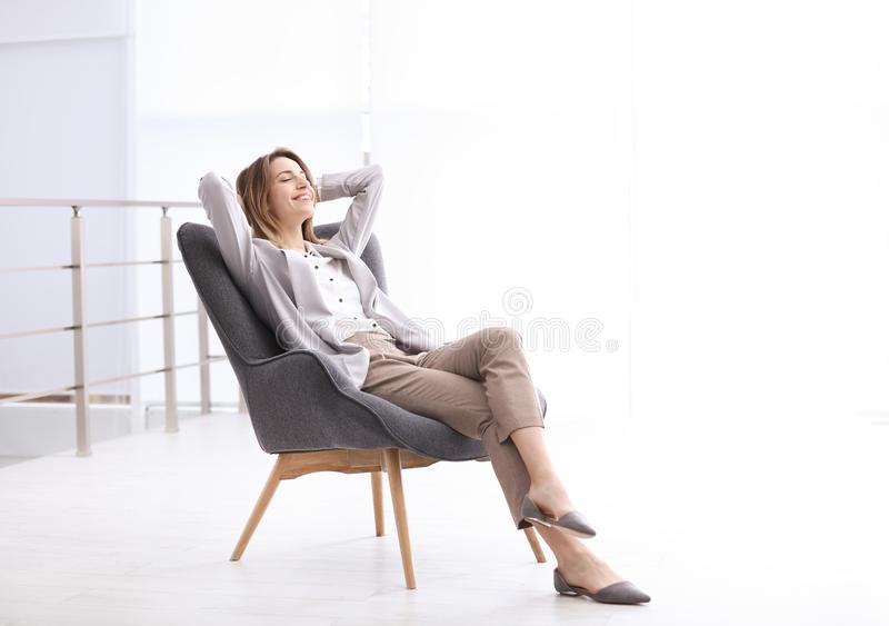 放松在扶手椅子的美丽的年轻女实业家户内 库存照片