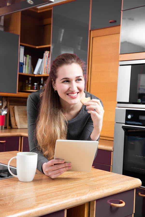 放松在拿着的愉快的华美的女孩一种片剂在厨房里 库存照片