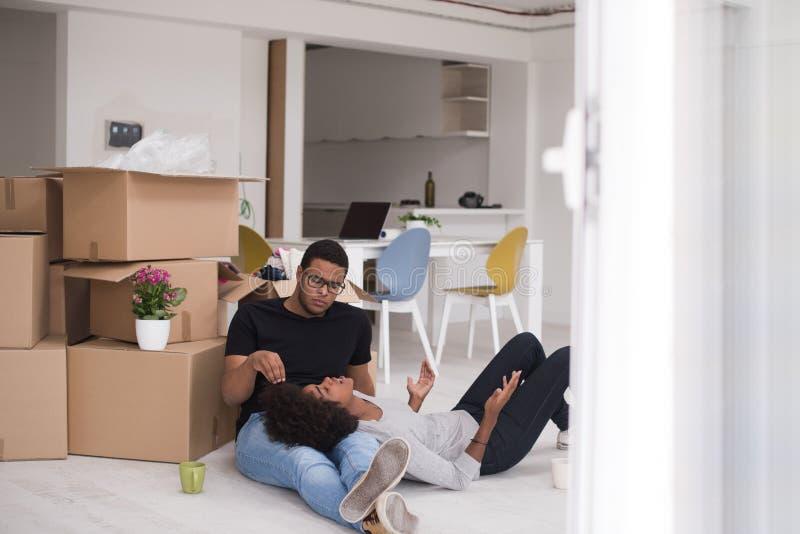 放松在新房里的非裔美国人的夫妇 免版税库存照片