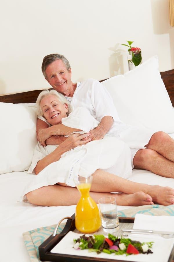 放松在旅馆客房佩带的长袍的资深夫妇 免版税库存照片