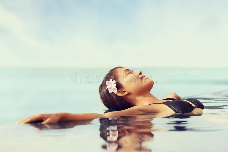 放松在无限游泳水池的豪华旅游胜地妇女 免版税库存图片