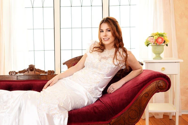 放松在昏晕的长沙发的新娘 图库摄影
