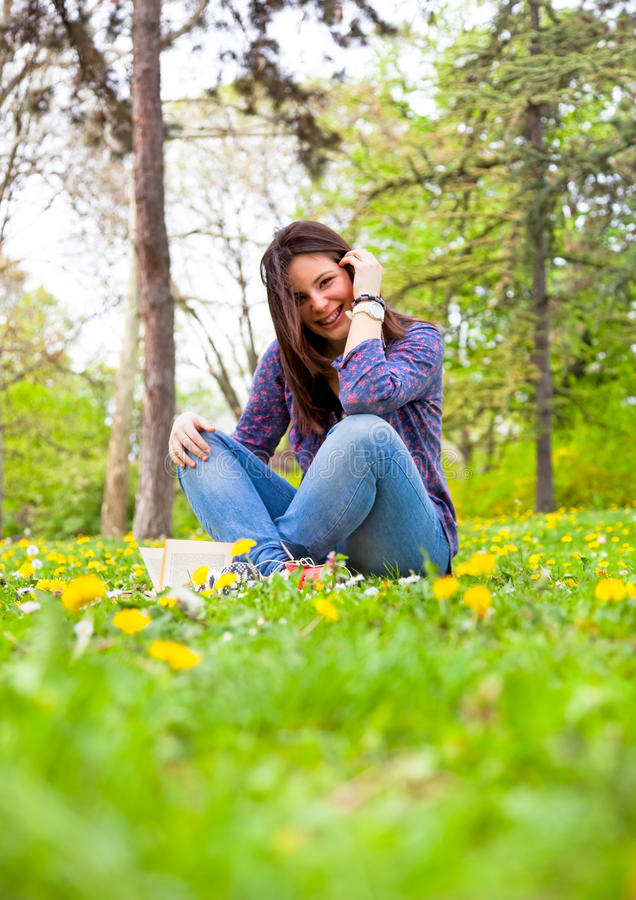 放松在春天公园的逗人喜爱的十几岁的女孩 库存图片