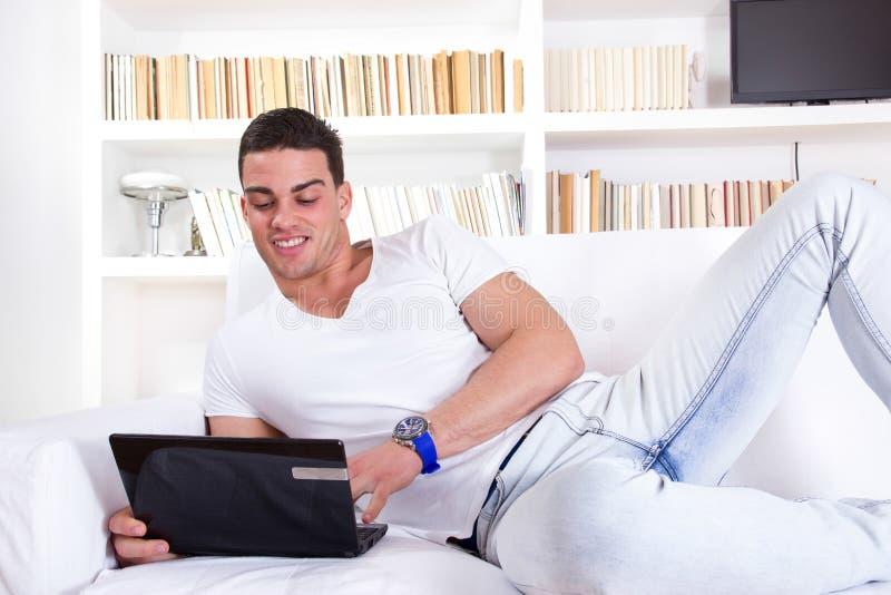 放松在有便携式计算机的沙发的人 免版税库存照片