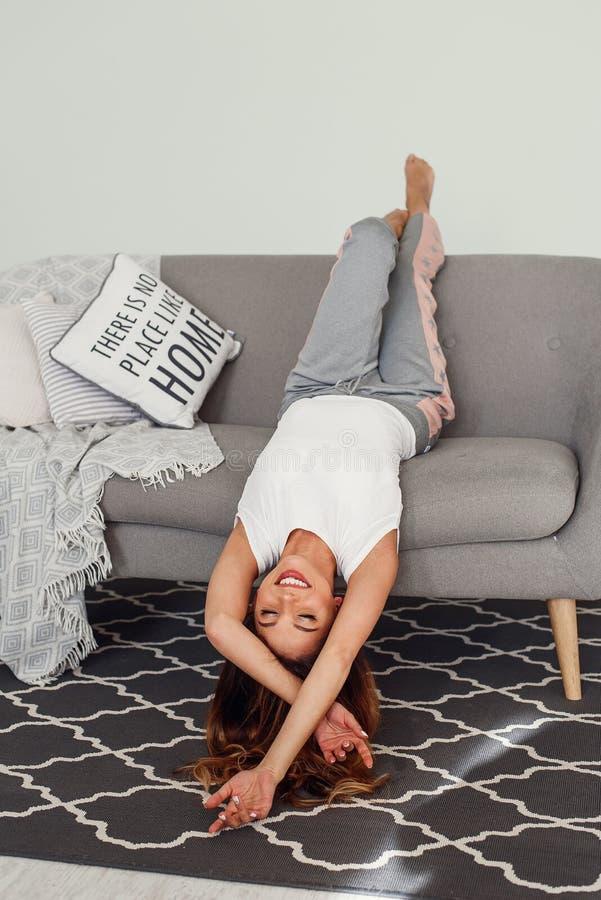 放松在有头的一个灰色长沙发的美女颠倒 逗人喜爱的女孩获得乐趣在舒适家在懒惰天 库存照片