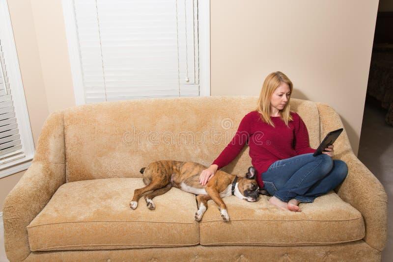 放松在有她的狗和电子设备的长沙发的妇女 库存照片