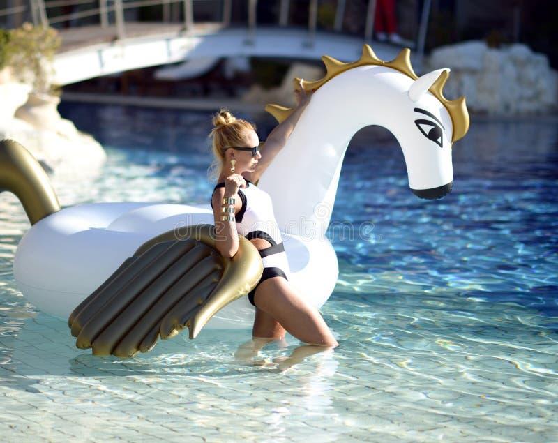 放松在有巨大的双的豪华游泳池度假旅馆里的妇女 免版税库存照片