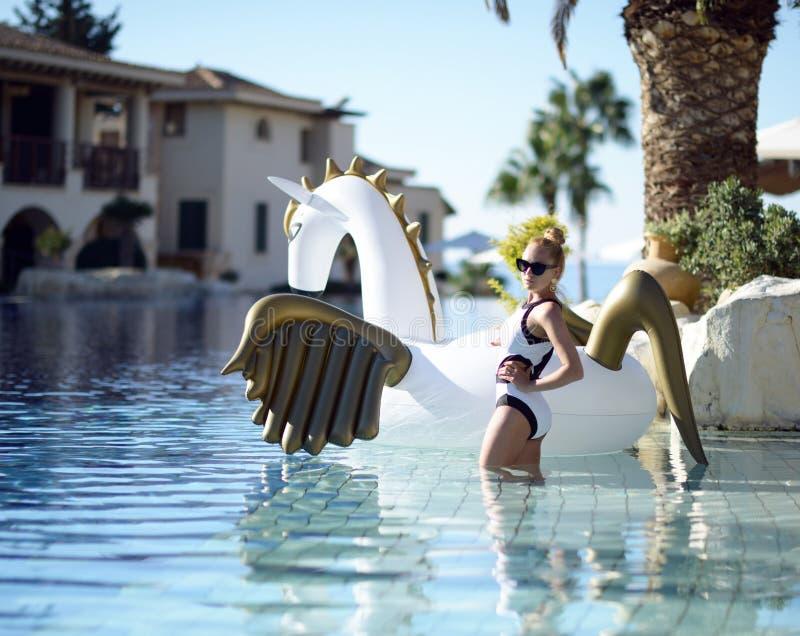 放松在有巨大的双的豪华游泳池度假旅馆里的妇女 库存照片