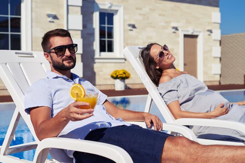 放松在有水池的现代房子前面的满意的夫妇 库存照片